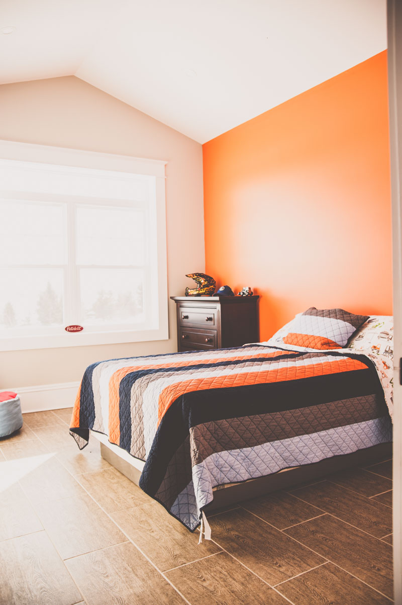Bright bedroom with orange accent wall