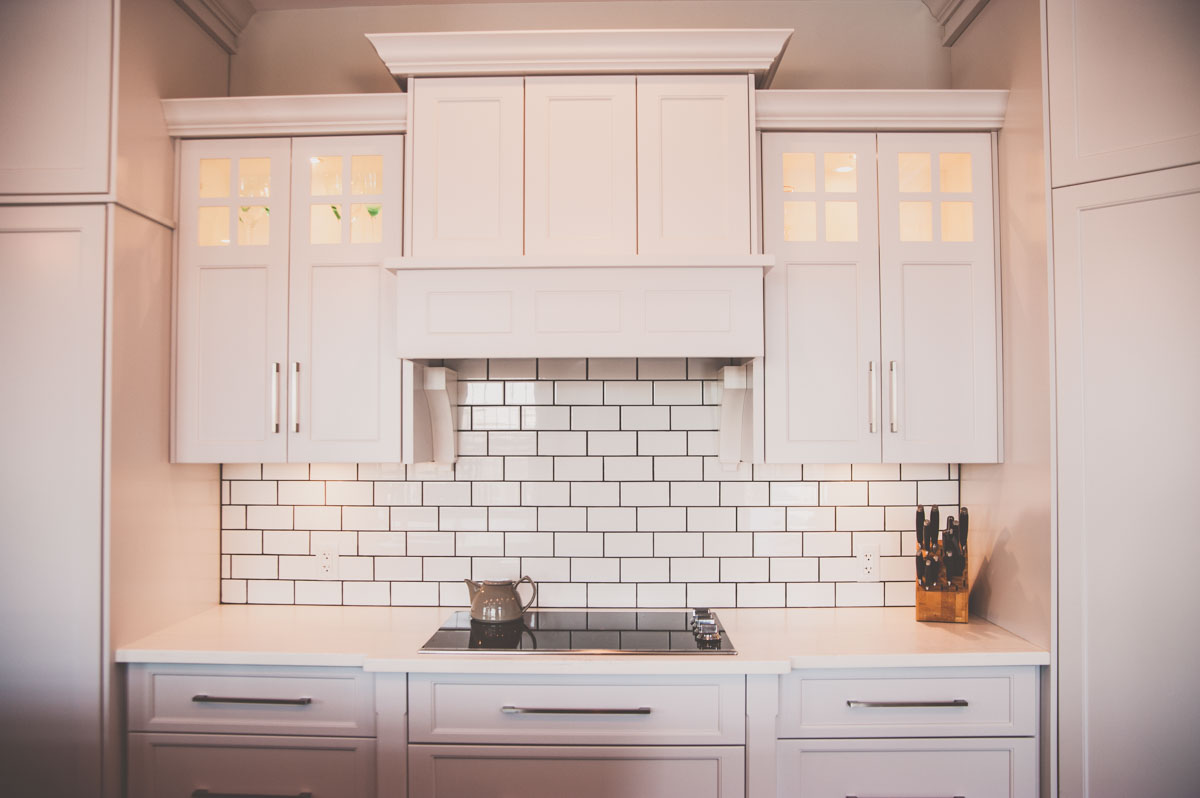 Custom home featuring kitchen backsplash, stovetop, and cabinetry in Summerfield